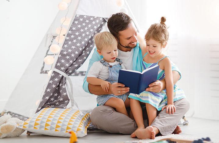 Familienvater liest den Kindern im Zelt vor