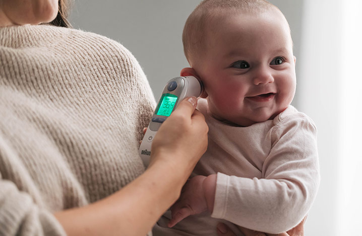Braun Ohrfieberthermometer hilft einem Elternteil, die Temperaturmesswerte zu verstehen, unter Berücksichtigung des Alters des Kindes