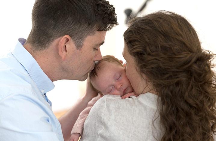 Mutter und Vater küssen den Kopf ihres Babys