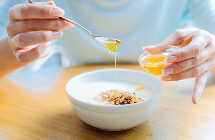 Nahaufnahme von Frauenhänden, die Honig zu Hafermehl hinzufügen