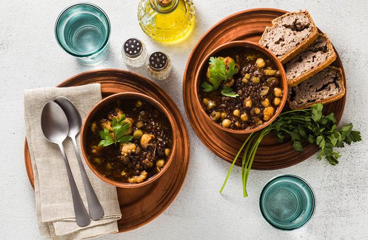Marokkanische schwarze Linsensuppe mit Kichererbsen und Blumenkohl in Schalen auf dem Tisch. Gesunde vegane Komfortnahrung mit Vollkornbrot.