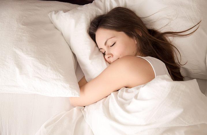 Eine junge Frau schläft gut in ihrem Bett und umarmt ein weiches weißes Kissen