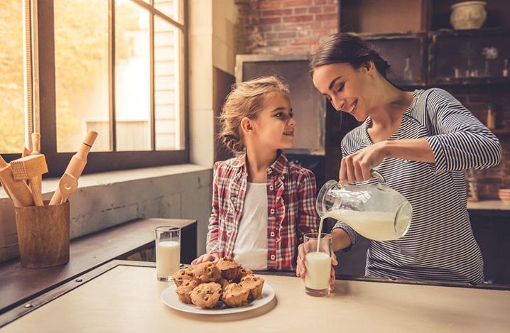 Süßes kleines Mädchen und ihre schöne Mutter lächeln, während sie Milch trinken