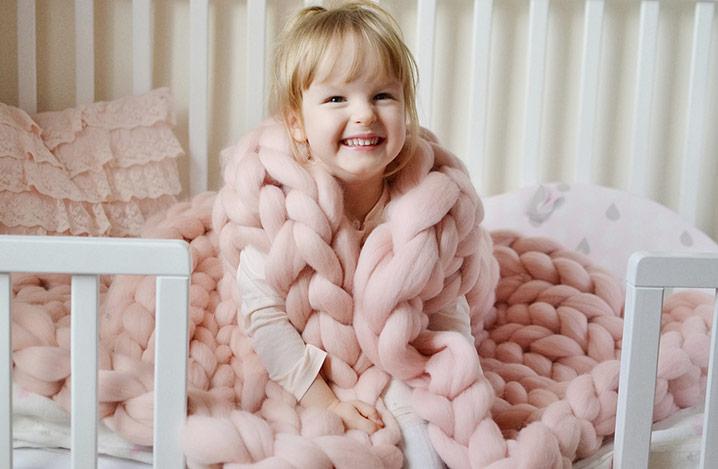 Glückliches blondes Mädchen, das mit einer rosa gestrickten riesigen Karodecke auf dem Bett sitzt