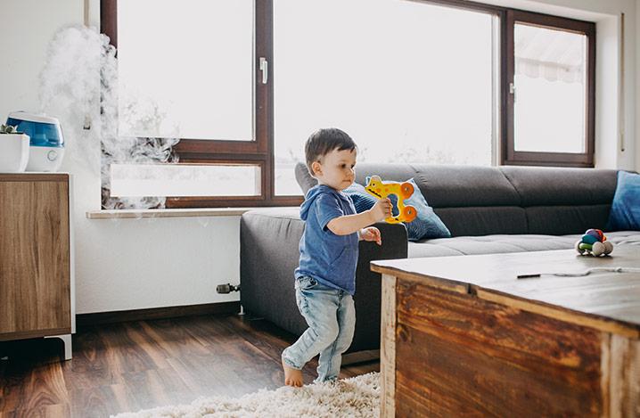Kleiner Junge mit einem Luftbefeuchter im Hintergrund