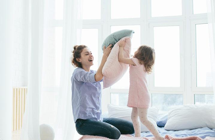 Junge Mutter und ihre kleine Tochter spielen mit Kissen auf dem Bett