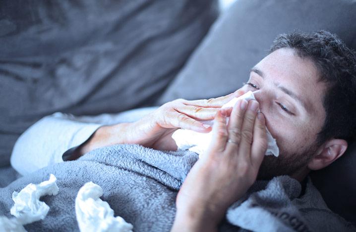 Nahaufnahme eines Mannes, der sich die Nase putzt, umgeben von zusammengeknüllten Taschentüchern