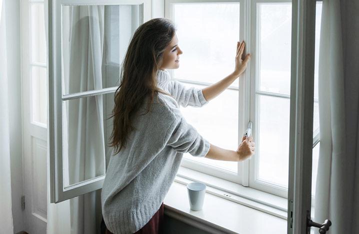 Frau, die das Fenster öffnet, um frische Luft hereinzulassen