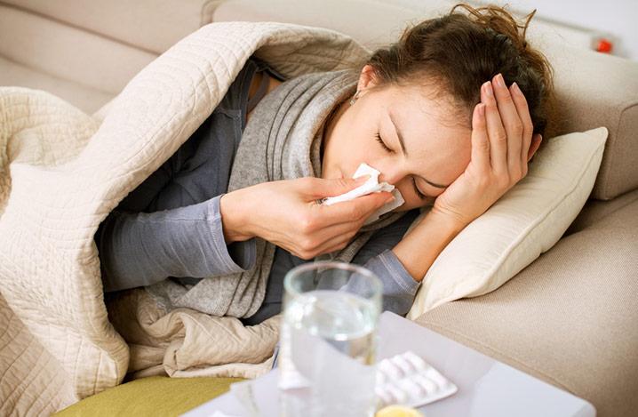 Junge Frau krank mit Hausmitteln auf dem Tisch