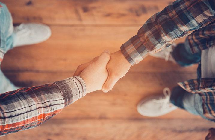 Nahaufnahme von zwei Männern beim Händeschütteln, Blick von oben