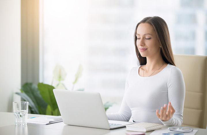 Frau, die beruhigende Meditation übt, sitzt an ihrem Schreibtisch vor einem Laptop