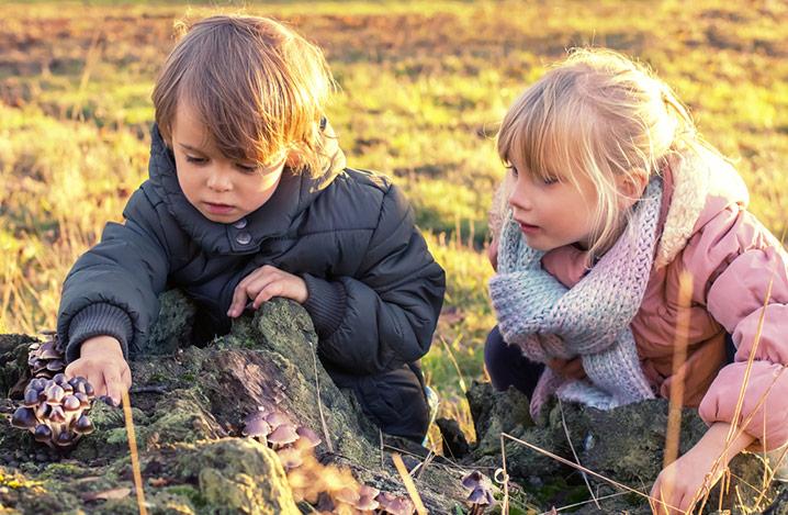 Junge und Mädchen in Wintermäntel gehüllt, kniend auf einem Feld, untersuchen einen Steinhaufen.
