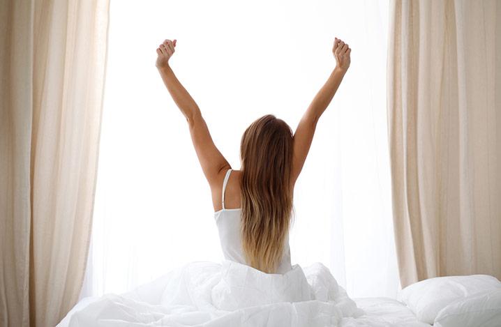 Frau sitzt auf dem Rand eines Bettes mit Blick auf das Fenster und streckt ihre Arme in die Luft.