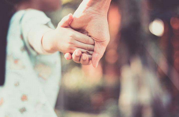 Verletztes Kind hält Händchen mit seiner Mutter