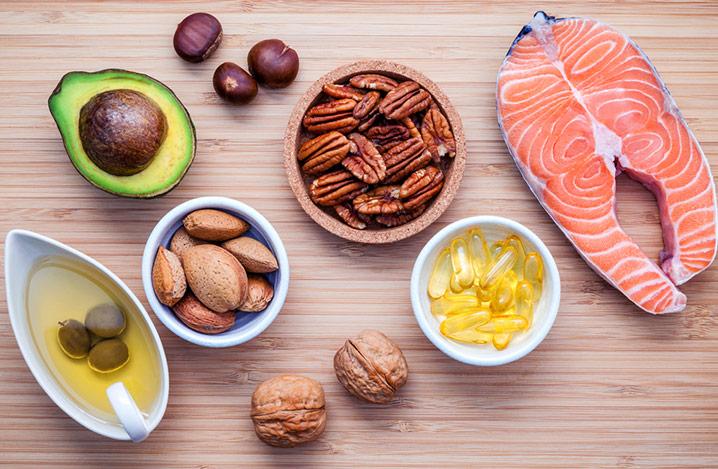 Auswahl der Nahrungsquellen für Omega-3-Fettsäuren und ungesättigte Fette. Pekannüsse, Haselnüsse, Walnüsse, Olivenöl, Fischöl, Lachs auf Schneidbrett