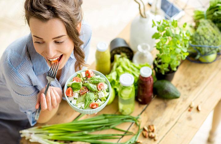 Frau, die einen gesunden grünen Salat isst, sitzt an einem Tisch mit Gemüse und Öl darauf
