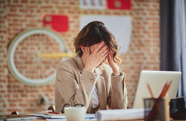 Frau sitzt an ihrem Schreibtisch mit den Händen am Kopf