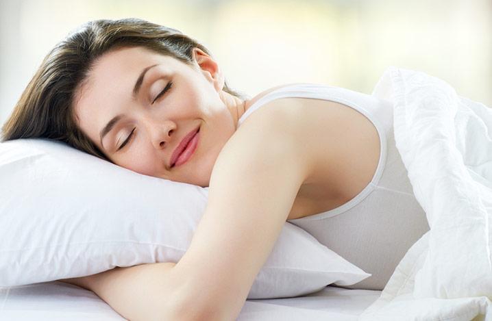 Frau schläft friedlich in einem Bett mit weißer Bettwäsche