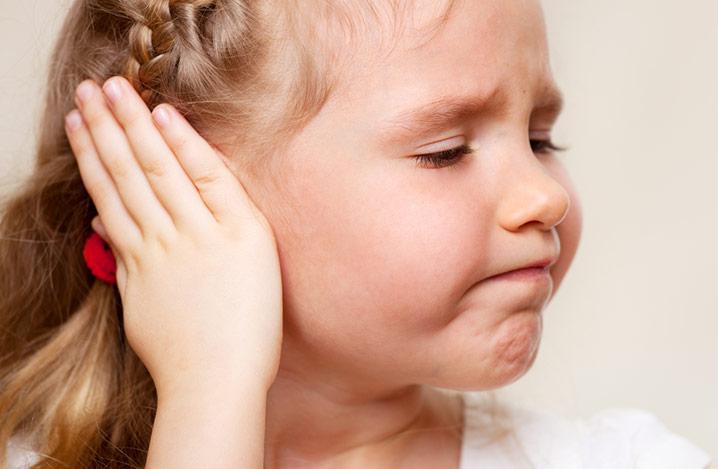 Ein kleines Mädchen hält ihre Hand über ihr Ohr, weil es unter Ohrenschmerzen leidet