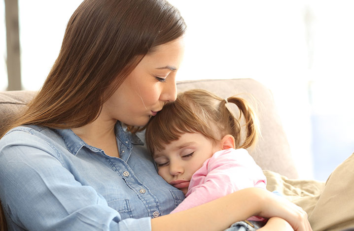 Nahaufnahme des Porträts einer Mutter in warmen Licht, die ihr schlafendes Töchterchen auf einem Sofa im Wohnzimmer küsst