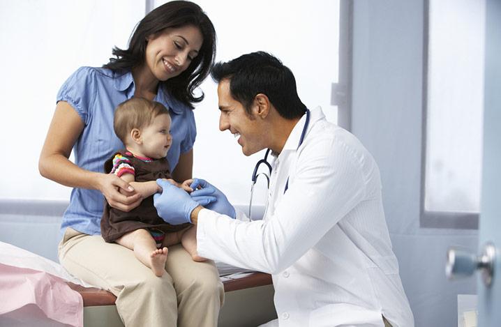Arzt in der Praxis untersucht kleines Mädchen