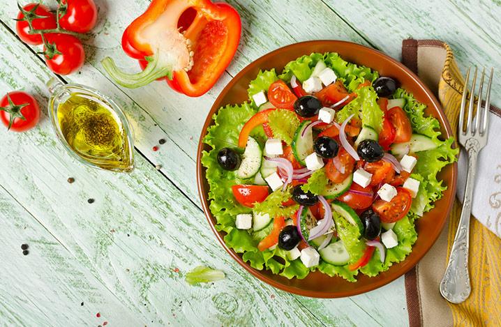 Griechischer Salat mit frischem Gemüse, Schafskäse und schwarzen Oliven auf einer Holztischplatte