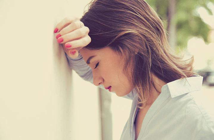 Porträt einer gestressten, traurigen jungen Frau im Freien, die ihren Arm und Kopf gegen eine Wand lehnt.