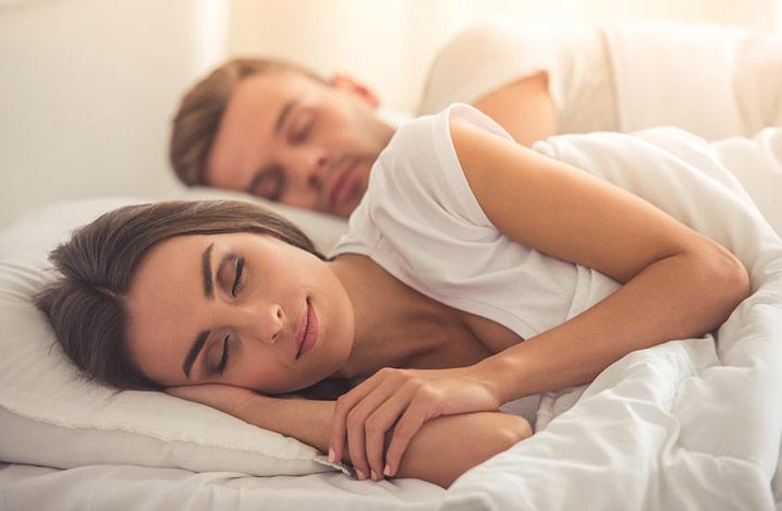 Seitenansicht eines schönen jungen Paares, das zu Hause im Bett schläft.