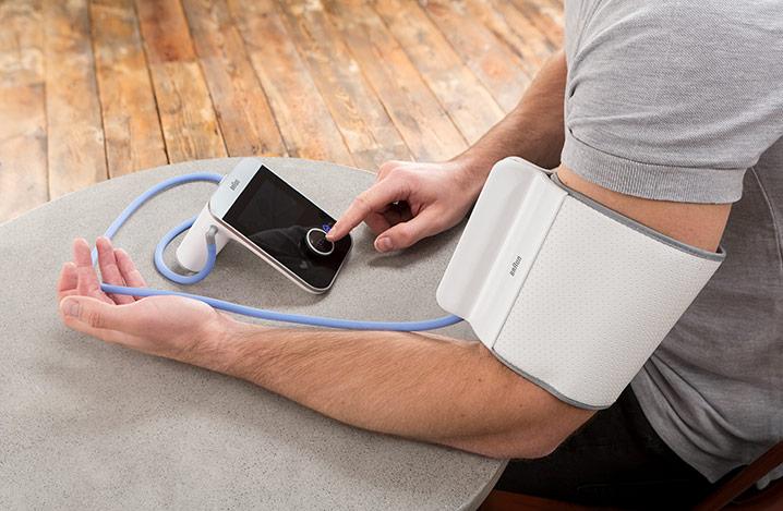 Mann am Tisch mit einem Arm-Blutdruckmessgerät
