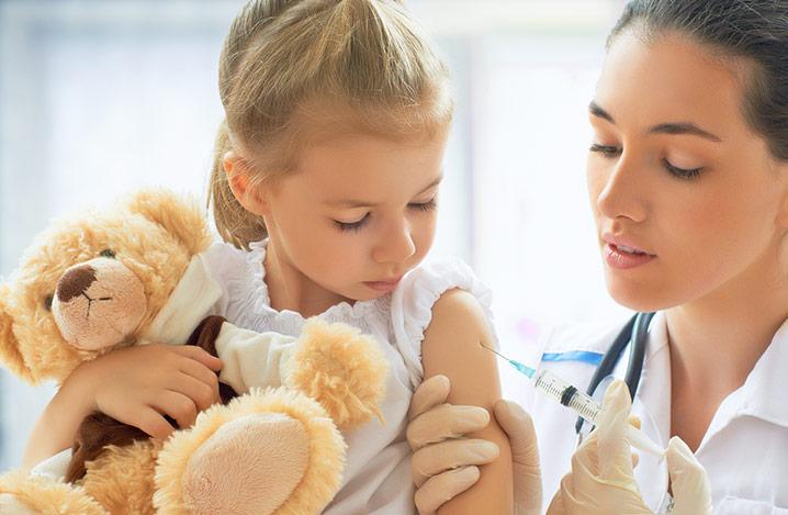 Arzt bei der Untersuchung und Impfung eines Kindes in einem Krankenhaus