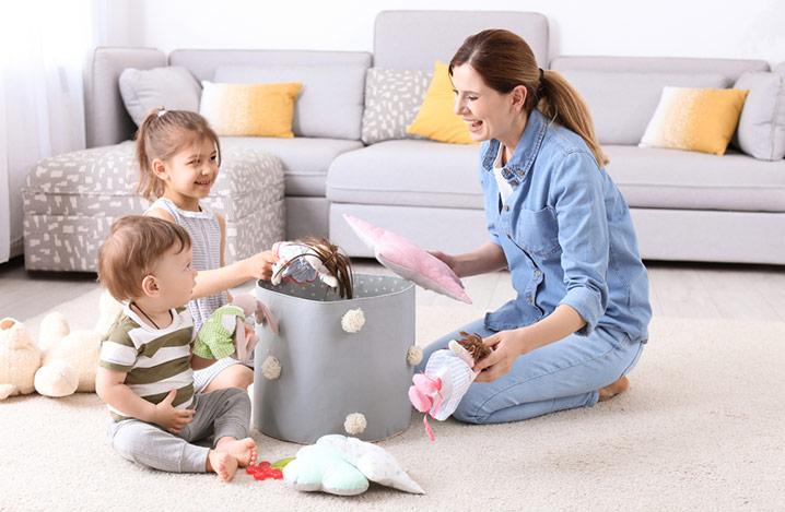 Mutter und Kinder heben Spielzeug auf, nachdem sie zu Hause gespielt haben