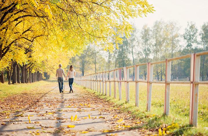 Paar spaziert durch einen Park im Herbst.