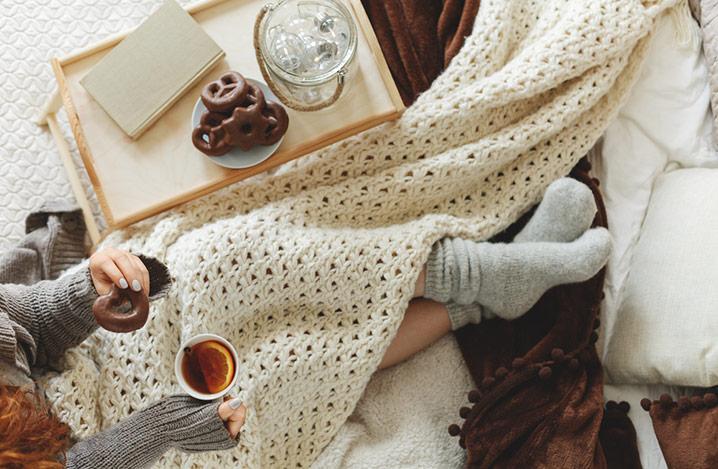 Junge Frau, die sich im Bett zugedeckt hat und warme Kleidung trägt