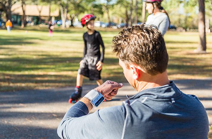 Das Braun iCheck 7 Blutdruckmessgerät wird von einem Mann in einem Park getragen.