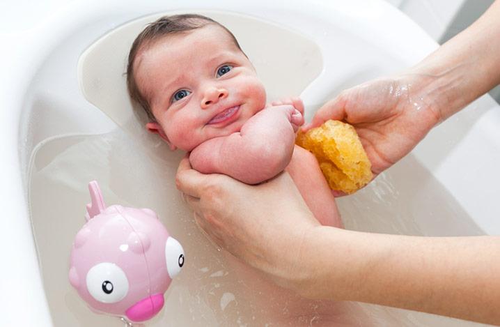 Neugeborenes wird von Mutter in Baby-Badewanne gebadet