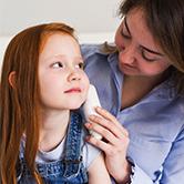 Petite fille à qui la mère prend la température auriculaire avec un thermomètre Braun