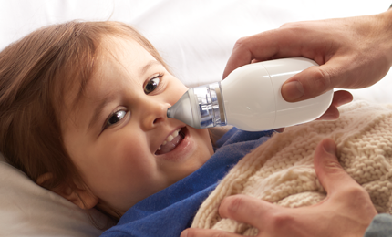Braun BNA100CA Electric Nasal Aspirator is used on a lying-down toddler