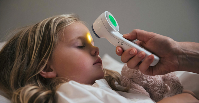 Little girl sleeping while her temperature is being taken on no touch mode with Braun No Touch with Age precision thermometer