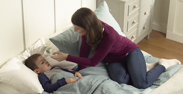 A mom is measuring her son's temperature with BNT400CA No Touch + Forehead Thermometer