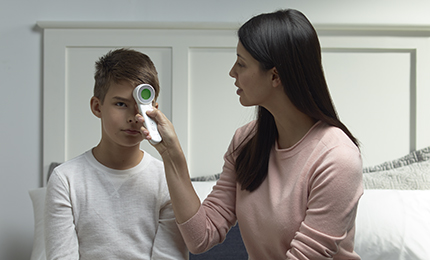 A mom is measuring her son's temperature with Braun BNT400CA Touch + Forehead thermometer