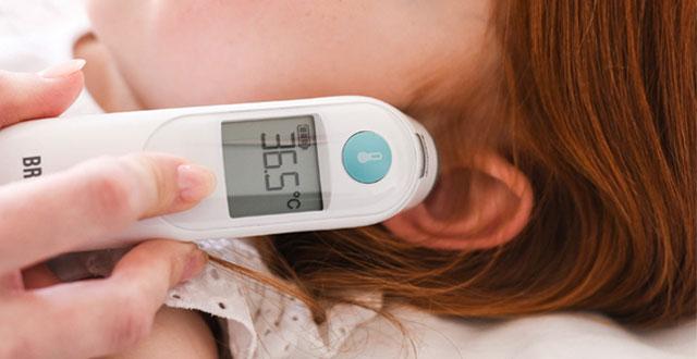 Mała czerwonowłosa dziewczynka leży podczas pomiaru temperatury