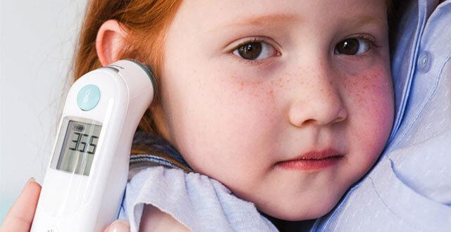 Mała czerwonowłosa dziewczynka ściska mamę podczas pomiaru temperatury